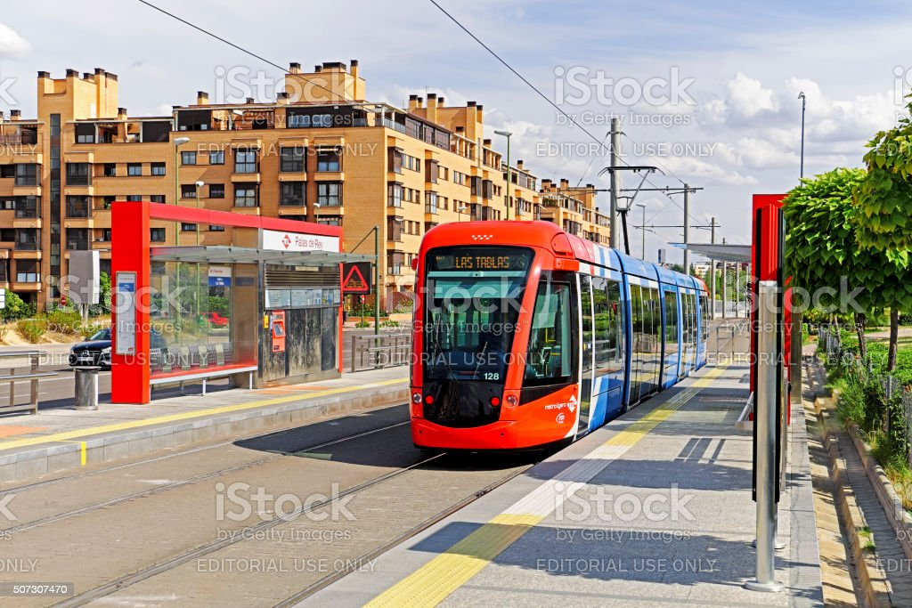 Madrid tram on Line ML-1 passes modern apartment building stock photo