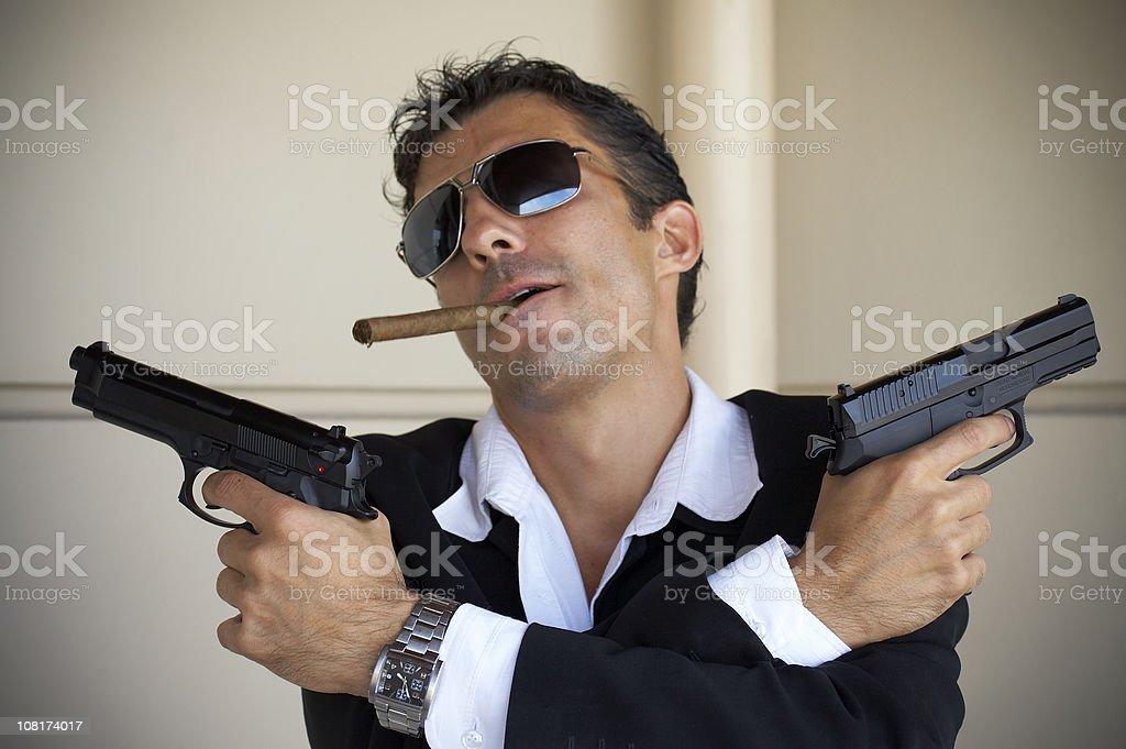 Mafia Boss Holding Guns and Smoking Cigar stock photo