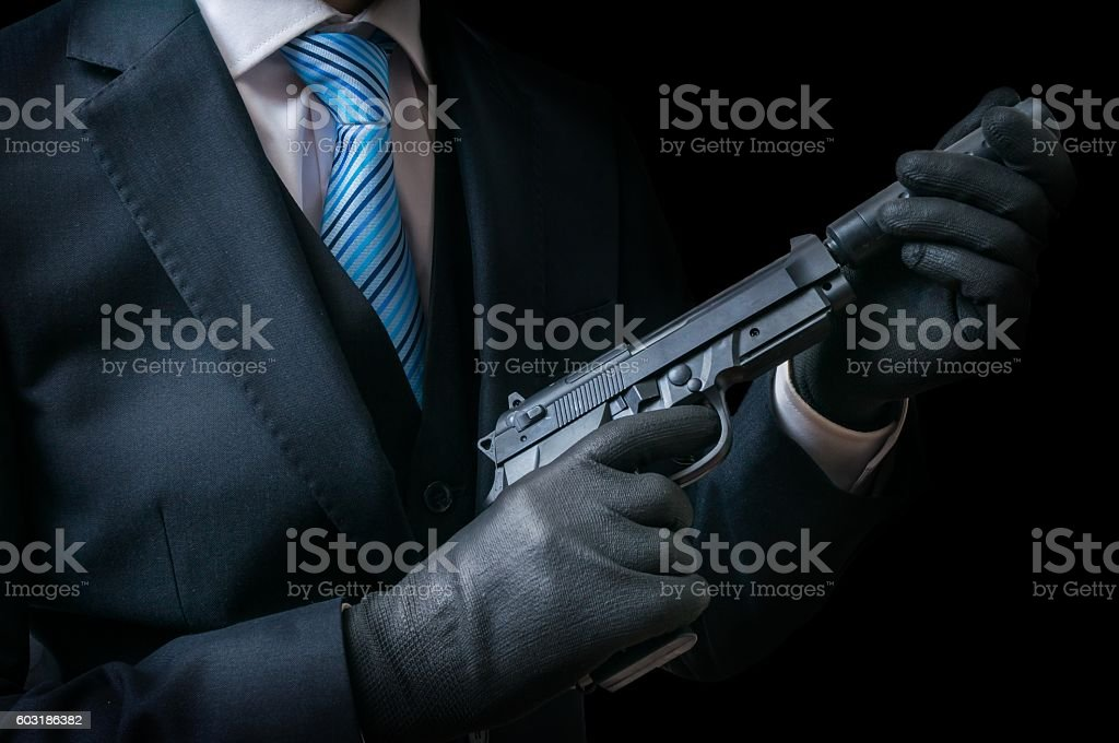 Mafia man holds pistol with silencer in hands. Low key. stock photo
