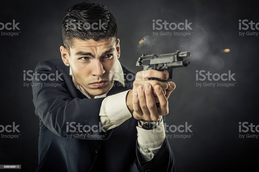 Mafia man shooting a gun stock photo