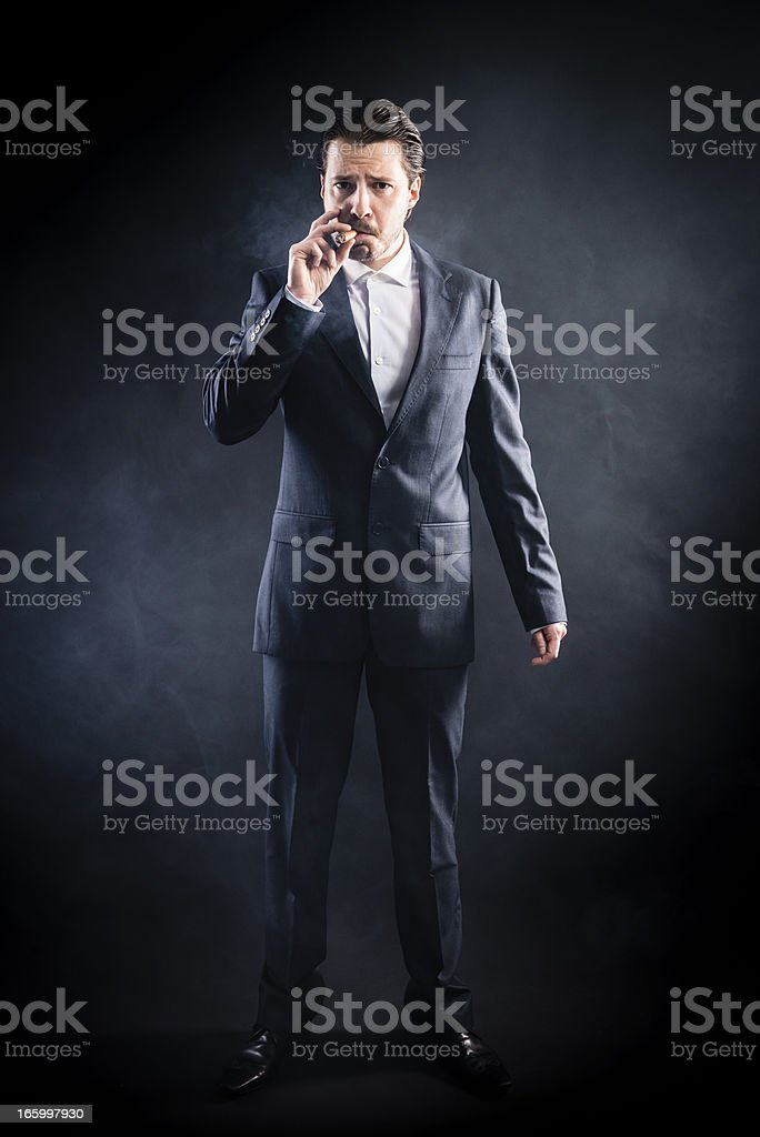 Mafia's man in suit smoking cigar, serious face, slicked hair stock photo