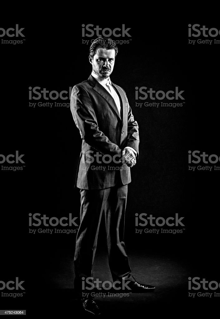 Mafioso, gangster, man in full suit, slicked back hair, displeased stock photo
