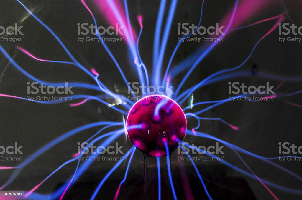 Magenta plasma ball with blue rays and magenta tips stock photo