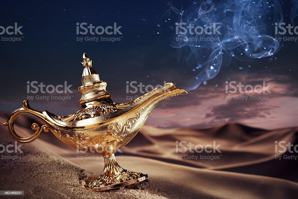Magic Aladdin's Genie lamp on a desert stock photo