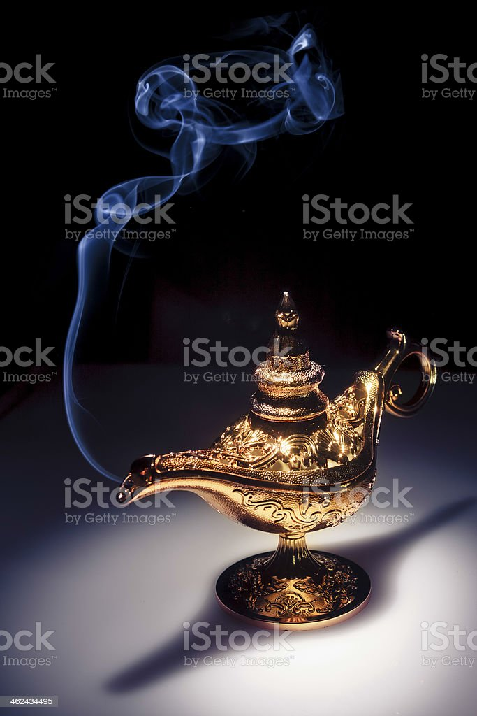 Magic Aladdin's Genie lamp on black with smoke stock photo
