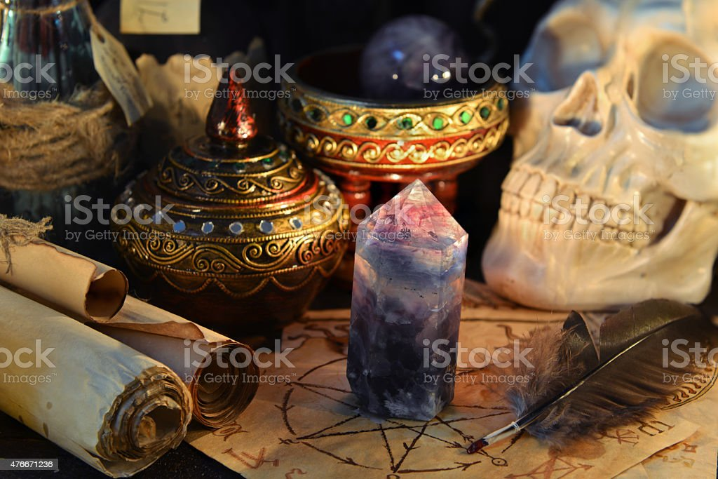Magic crystal stone and scary human skull in candle light stock photo