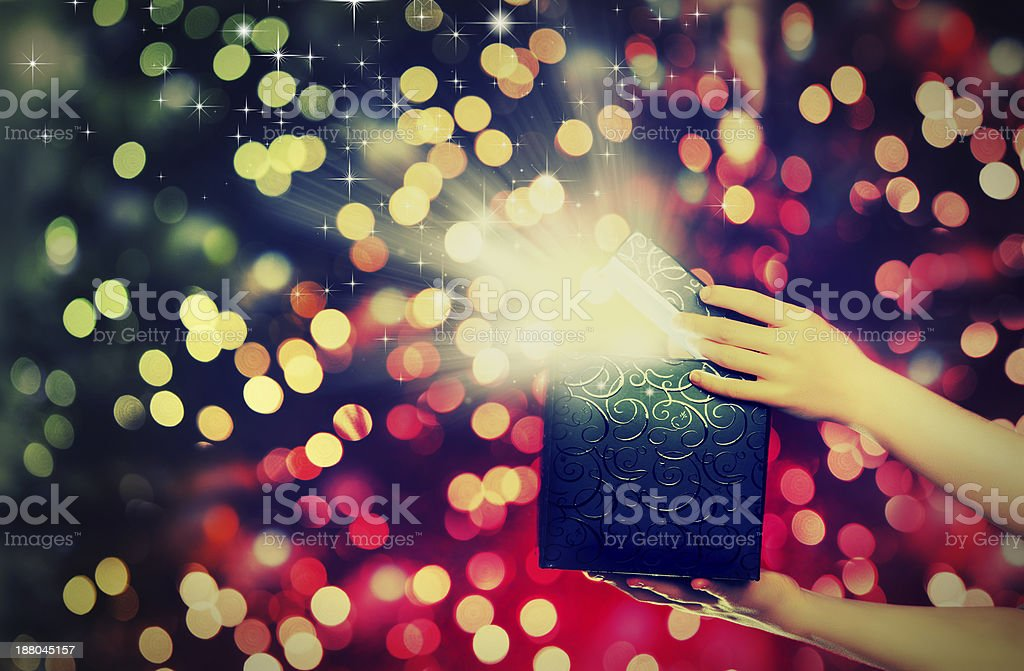 magic gift box with lights in their hands royalty-free stock photo