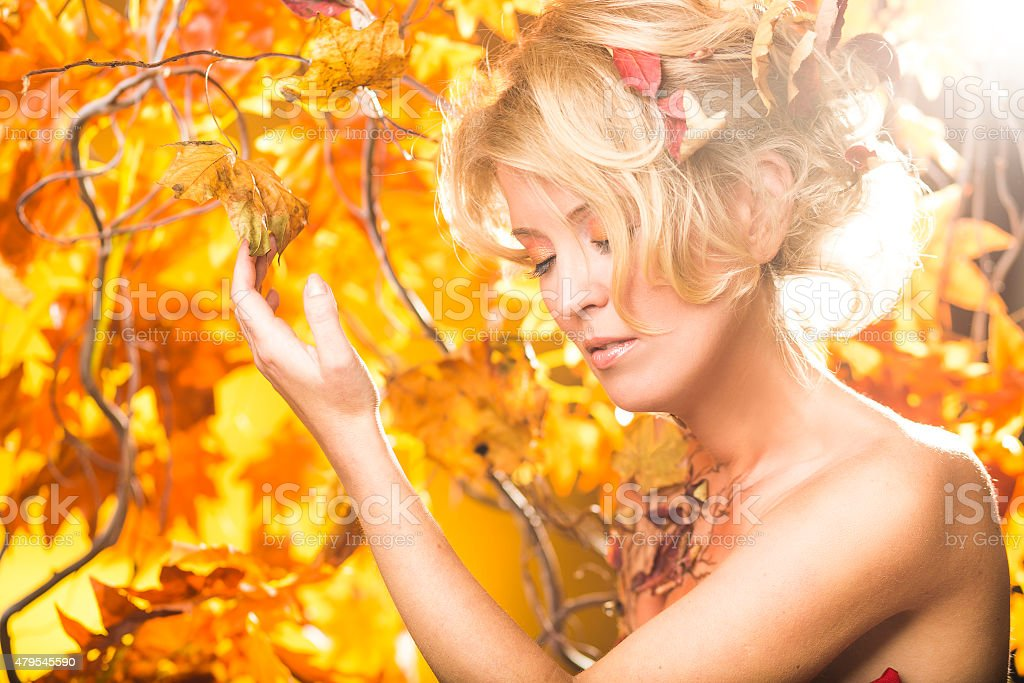 Magic gold autumn blonde girl portrait in leafs stock photo