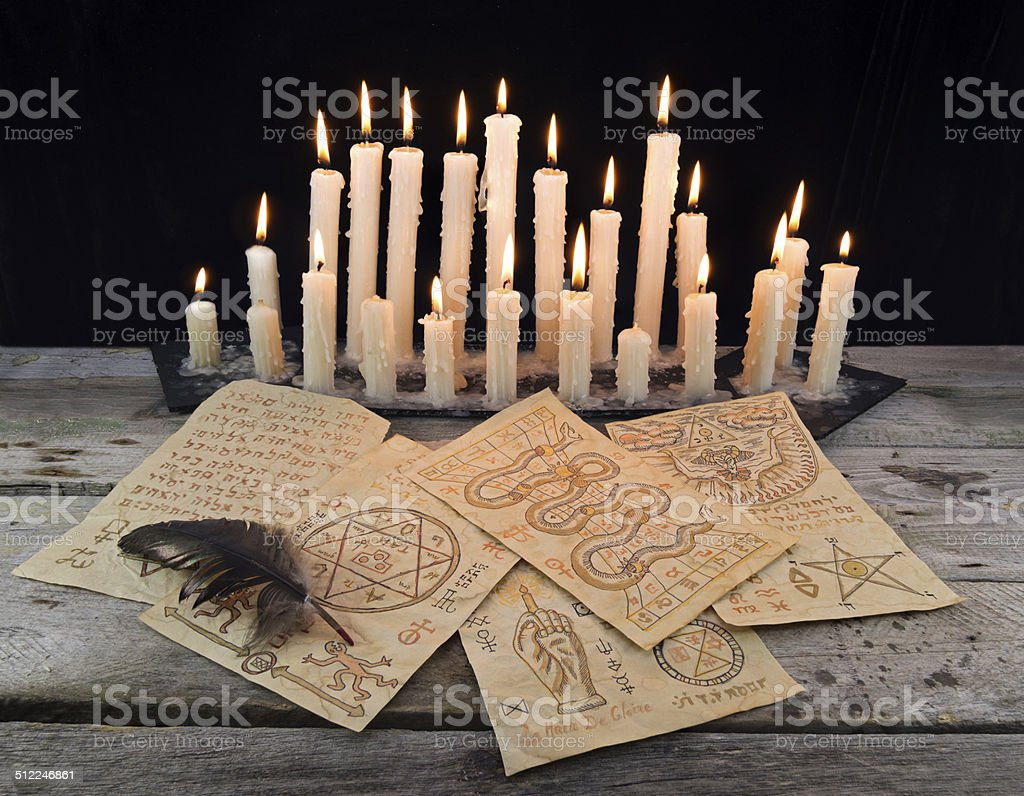 Magic papers with candles stock photo