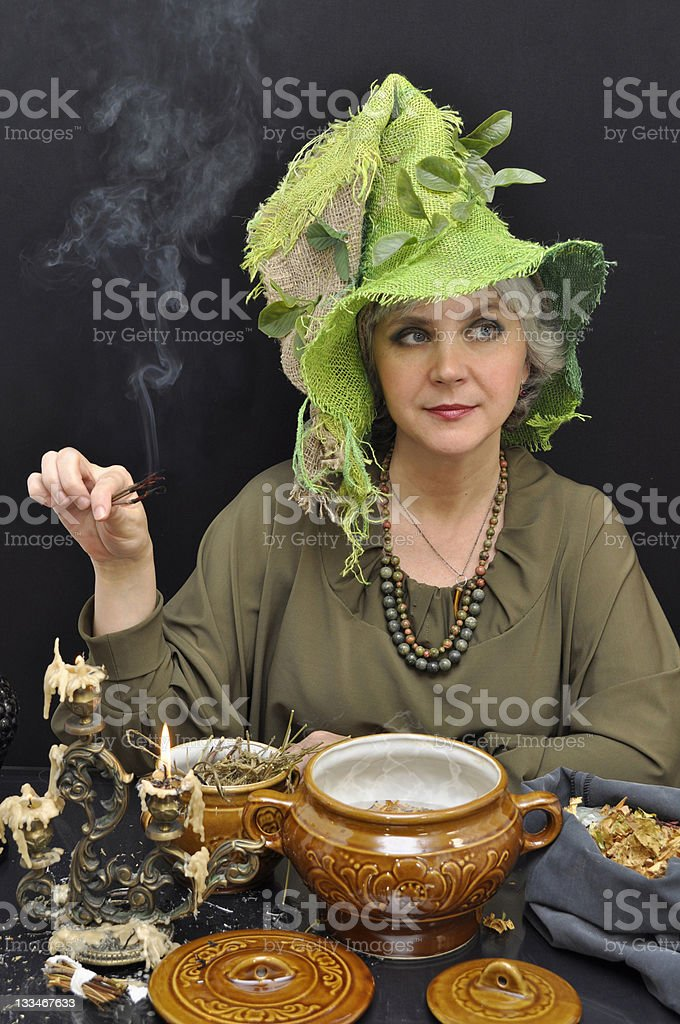 Magic woman in green hat with smoking twigs stock photo