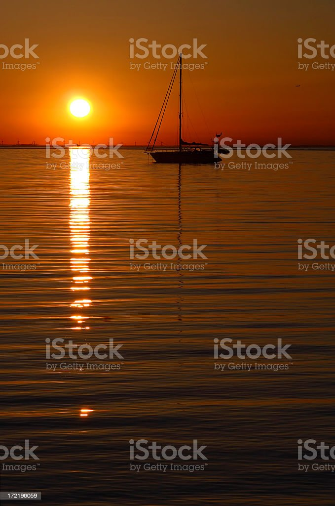 A magical sunset and a view of a small boat stock photo