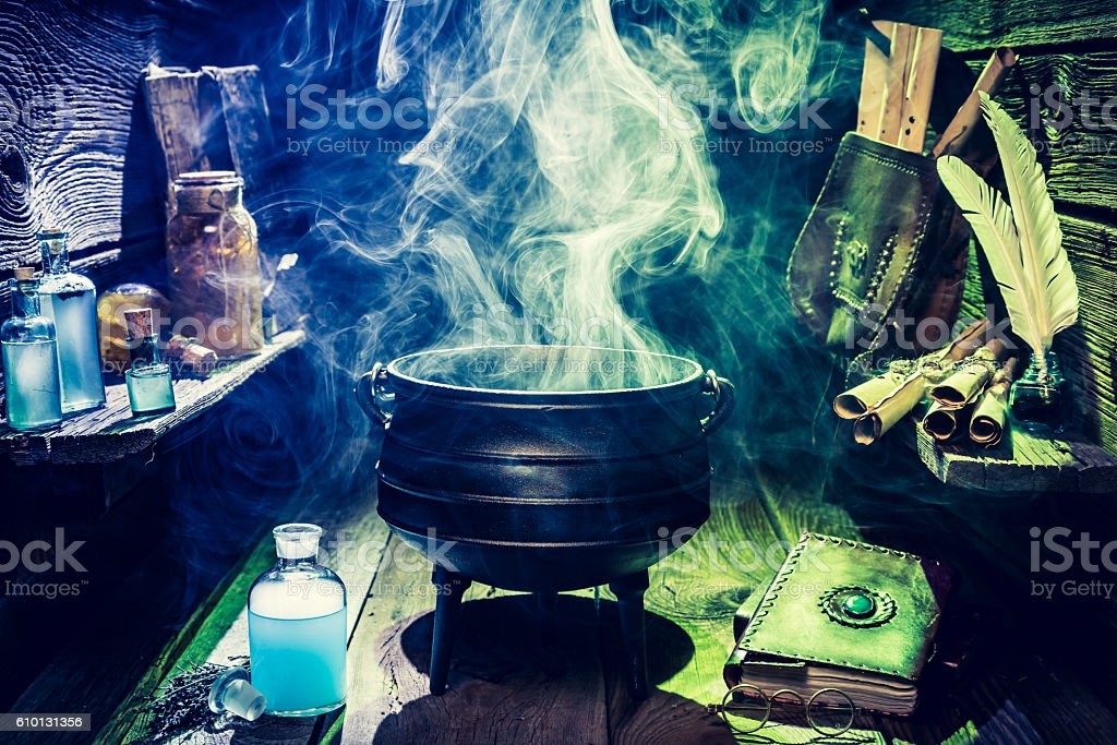 Magical witch pot with scrolls, books and blue potions stock photo
