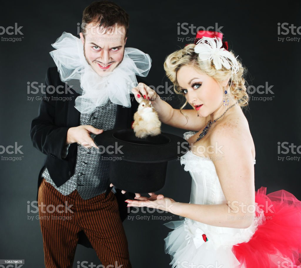 Magician and assistant pulling a bunny out of hat stock photo
