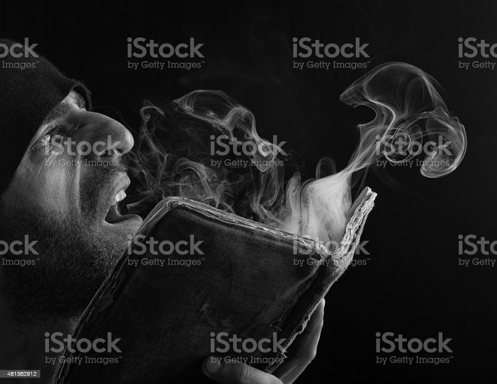 Magician blowing smoke ower antique book stock photo