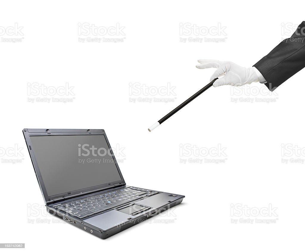 Magician holding a magic wand over the laptop stock photo