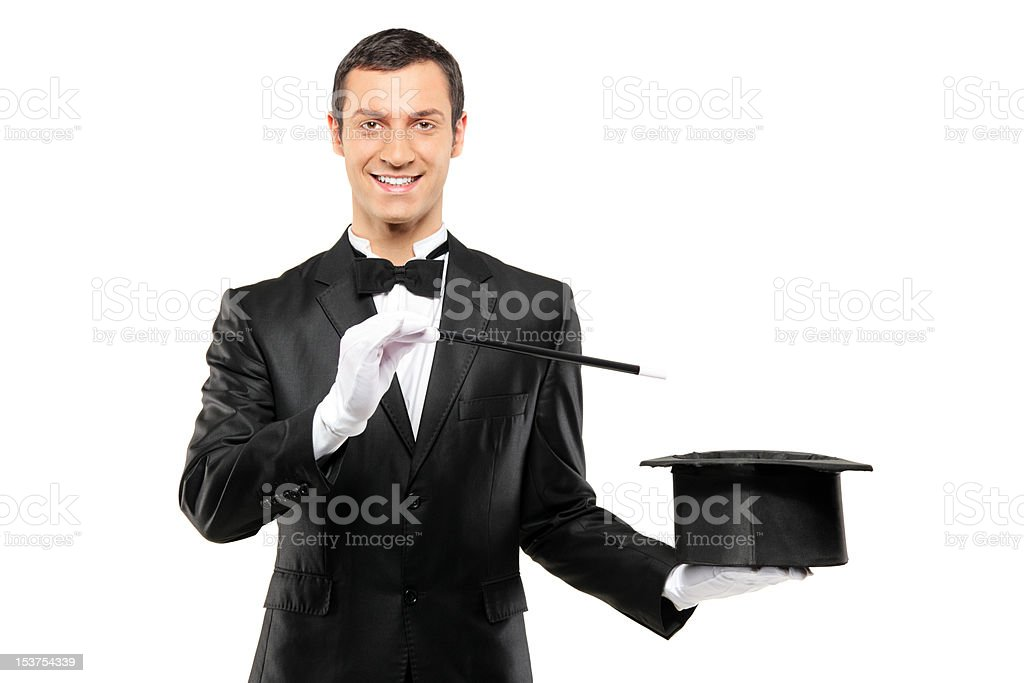 Magician holding an empty top hat and magic wand stock photo