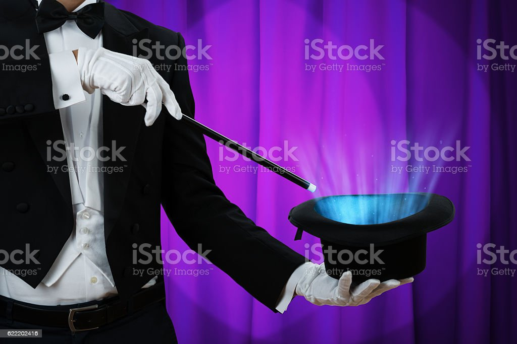 Magician Holding Wand Over Illuminated Hat stock photo