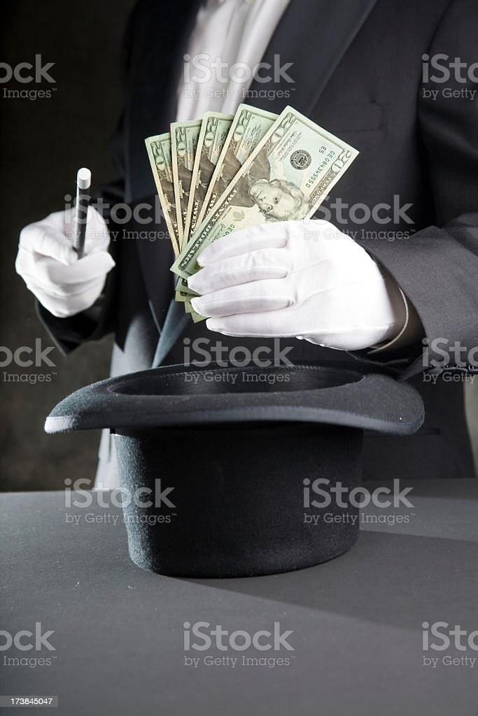 Magician man pulling money from hat stock photo