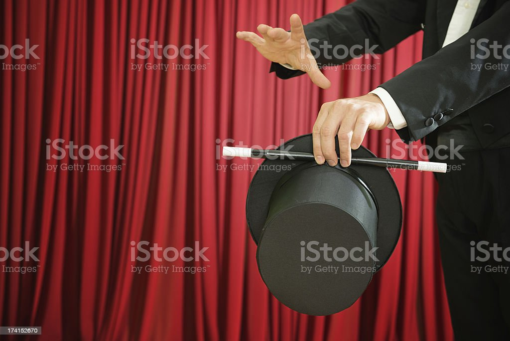 Magician performing with top hat and magic wand stock photo