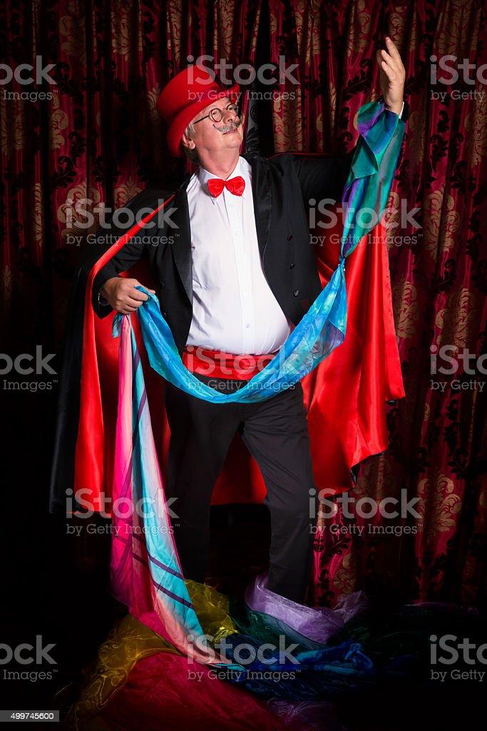 Magician pulling colorful handkerchiefs stock photo
