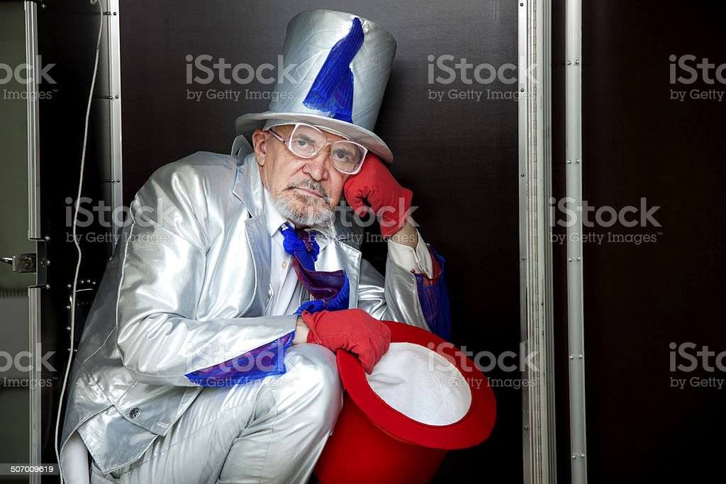 Magician sitting in a box stock photo