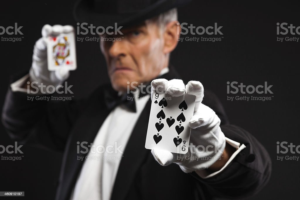 Magician with black suit and hat holding set of cards. stock photo