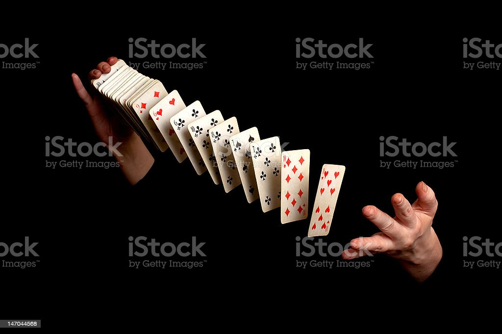 Magician with cards on black background stock photo