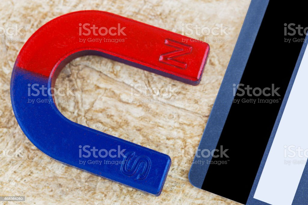 Magnet pulling credit card on fiber paper background stock photo