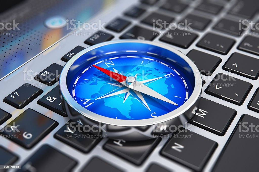 Magnetic compass on laptop keyboard stock photo