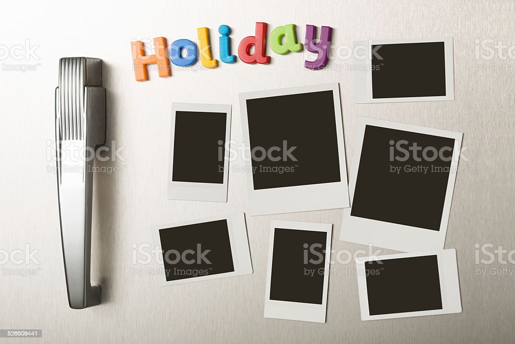 HOLIDAY magnetic letters and blank polaroid prints on fridge door stock photo
