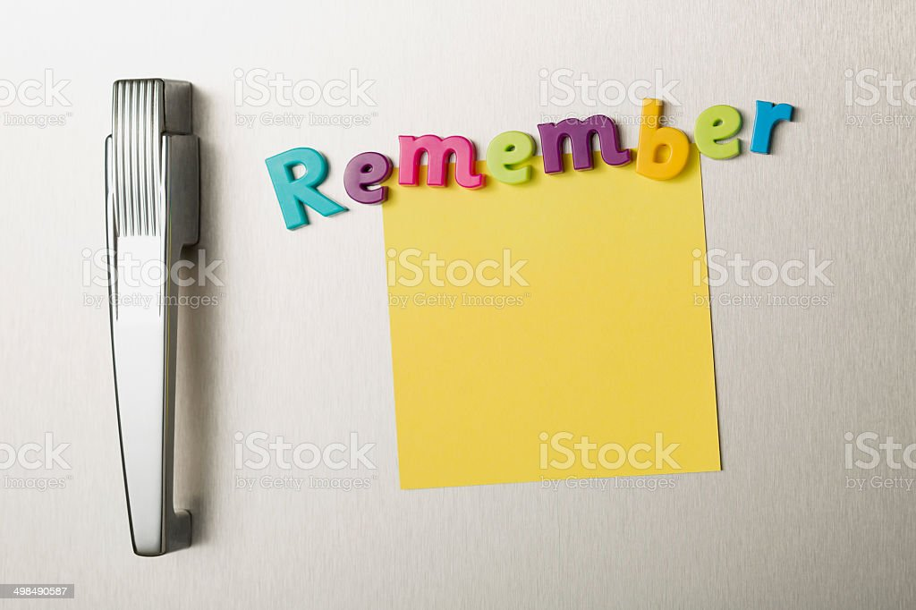 REMEMBER magnetic letters and post-it note on refrigerator door stock photo