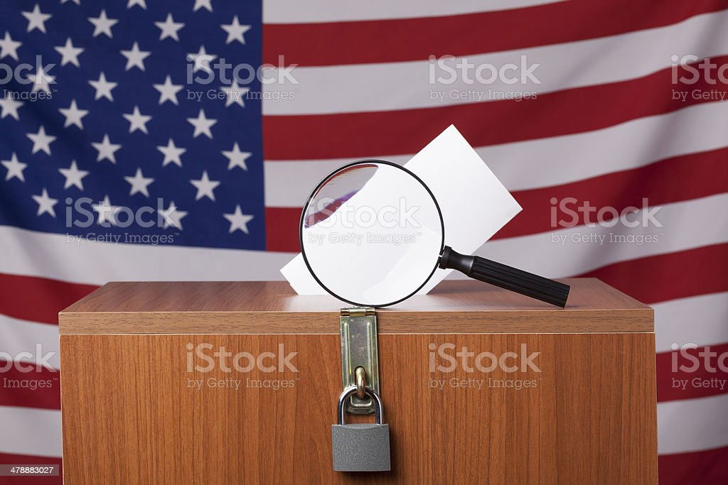 Magnfying glass on ballot box before American Flag royalty-free stock photo
