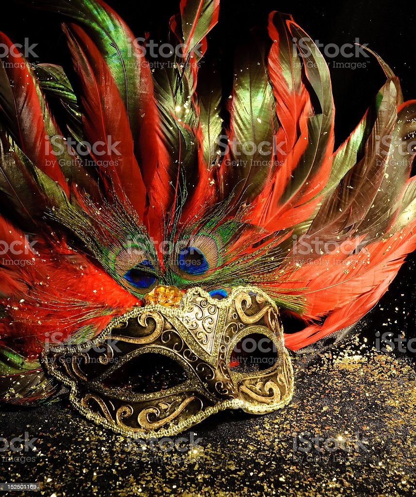 Magnificent gold mask with long feathers on black background stock photo