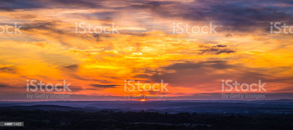Magnificent sunset golden skies dramatic cloudscape panorama over misty hills stock photo
