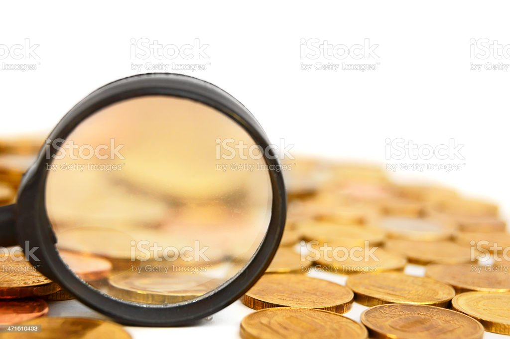 Magnifier and coins. On a white background. stock photo