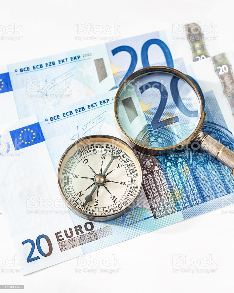 Magnifier and compass lying on euro bills royalty-free stock photo