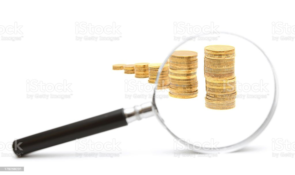 Magnifier and gold coins. On a white background. stock photo