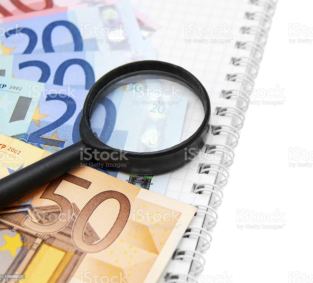 Magnifier and money on a notebook. royalty-free stock photo