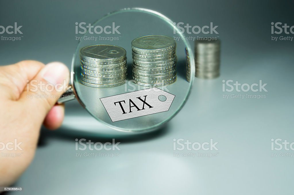 Magnifier, Tax Tag, and stack coins in the backdround stock photo