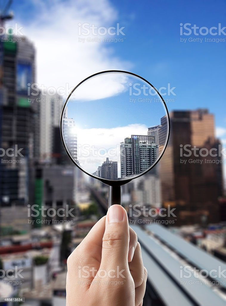 Magnifying glass and cityscape in focus, business vision stock photo