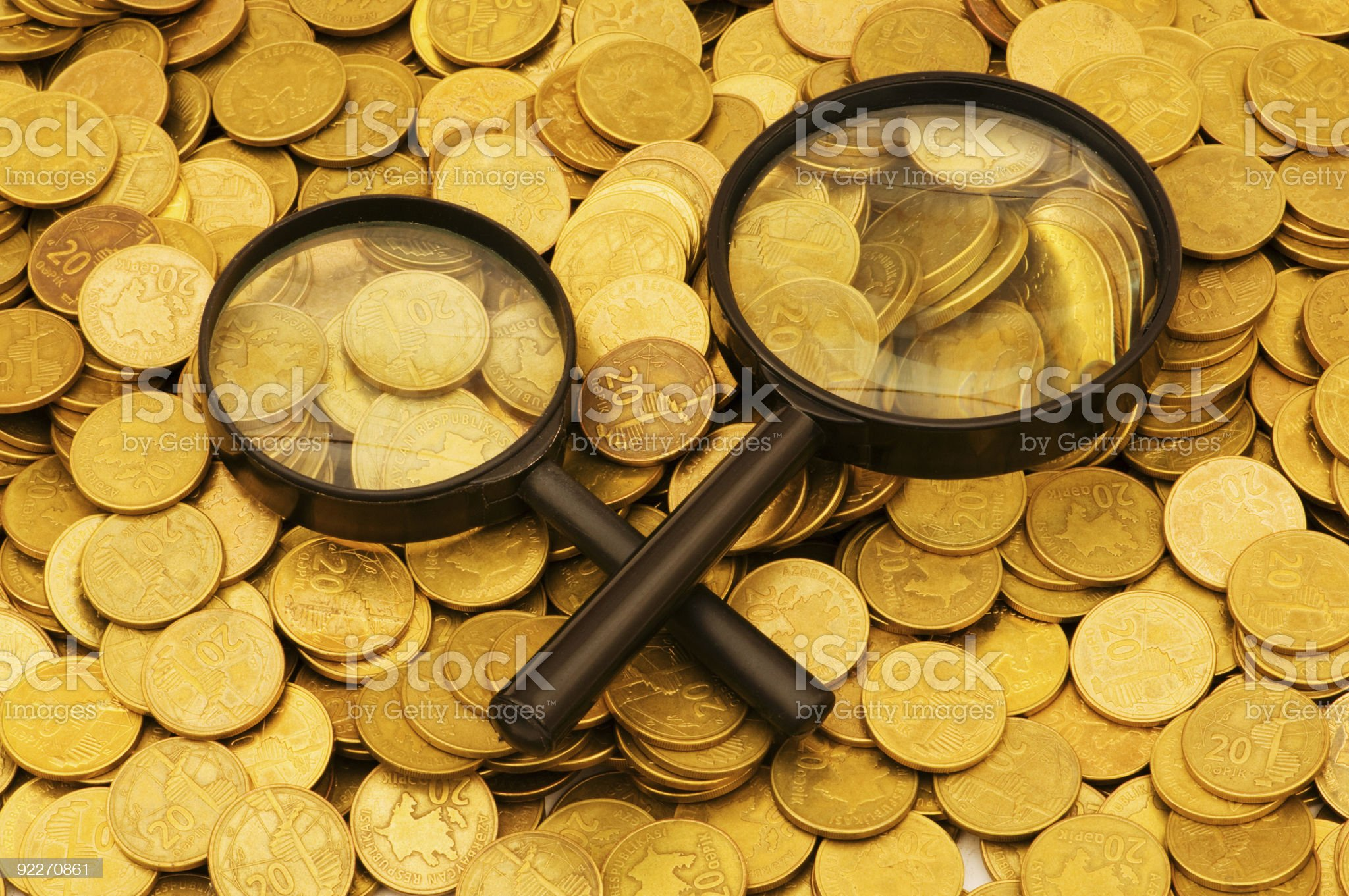 Magnifying glass and coins at the background royalty-free stock photo