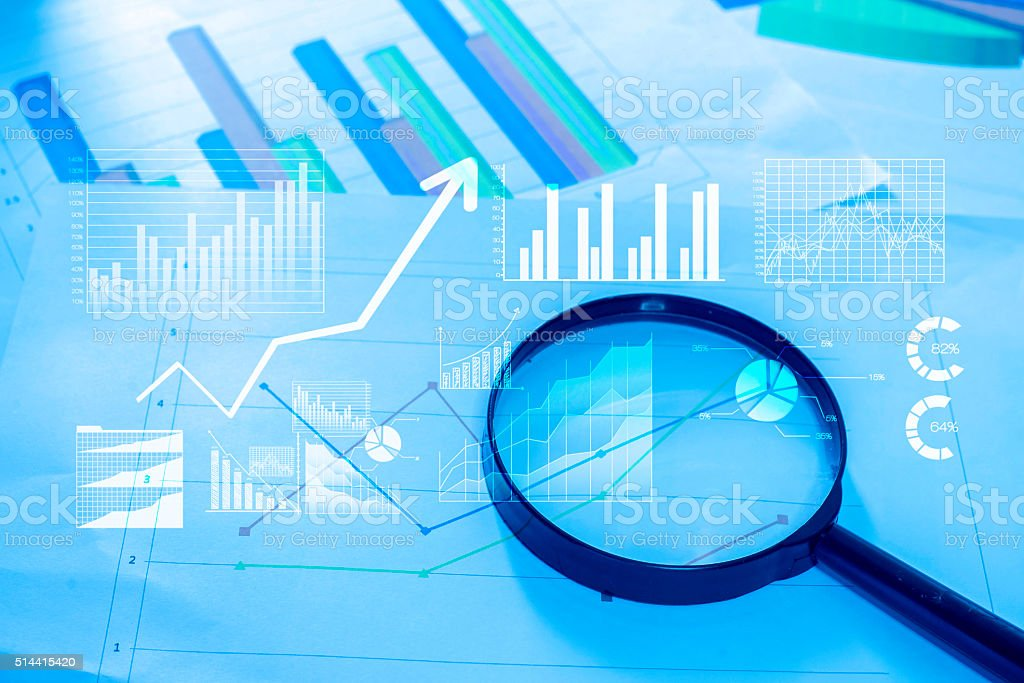 Magnifying glass and documents with analytics data lying on tabl stock photo