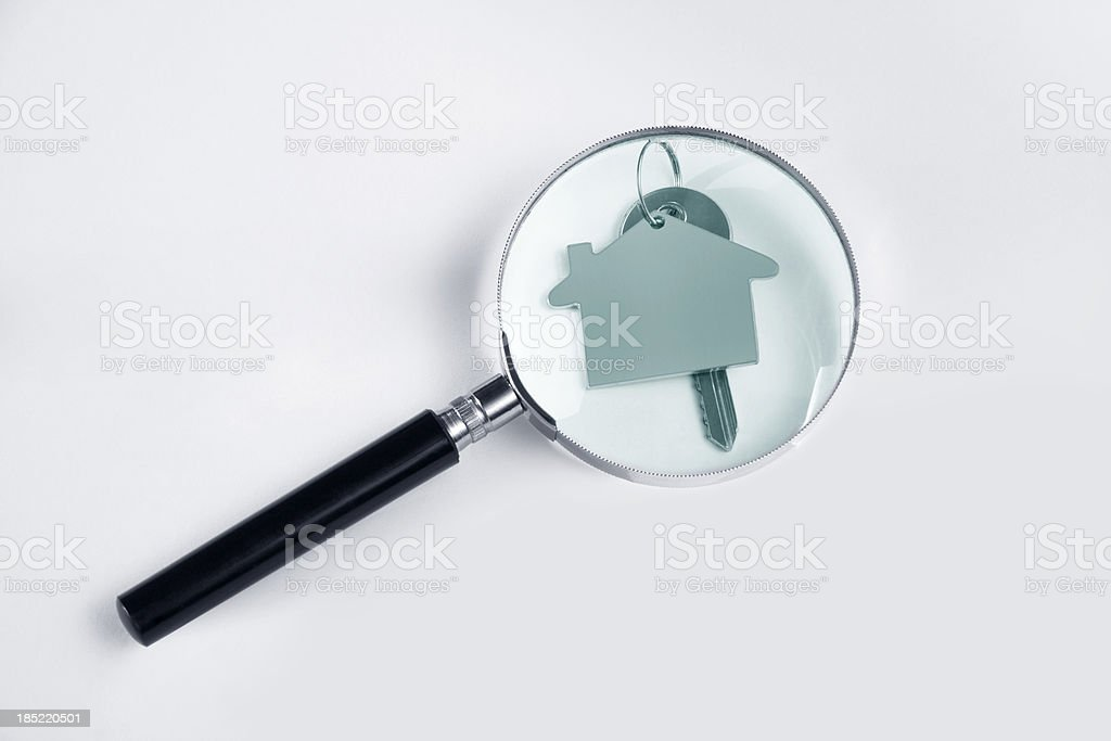 Magnifying glass and house key. royalty-free stock photo