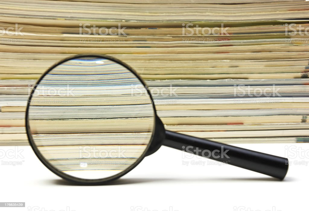 magnifying glass and stack of magazines royalty-free stock photo