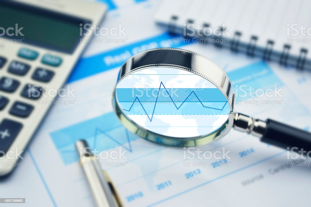 Magnifying glass, calculator and pen on financial graph stock photo