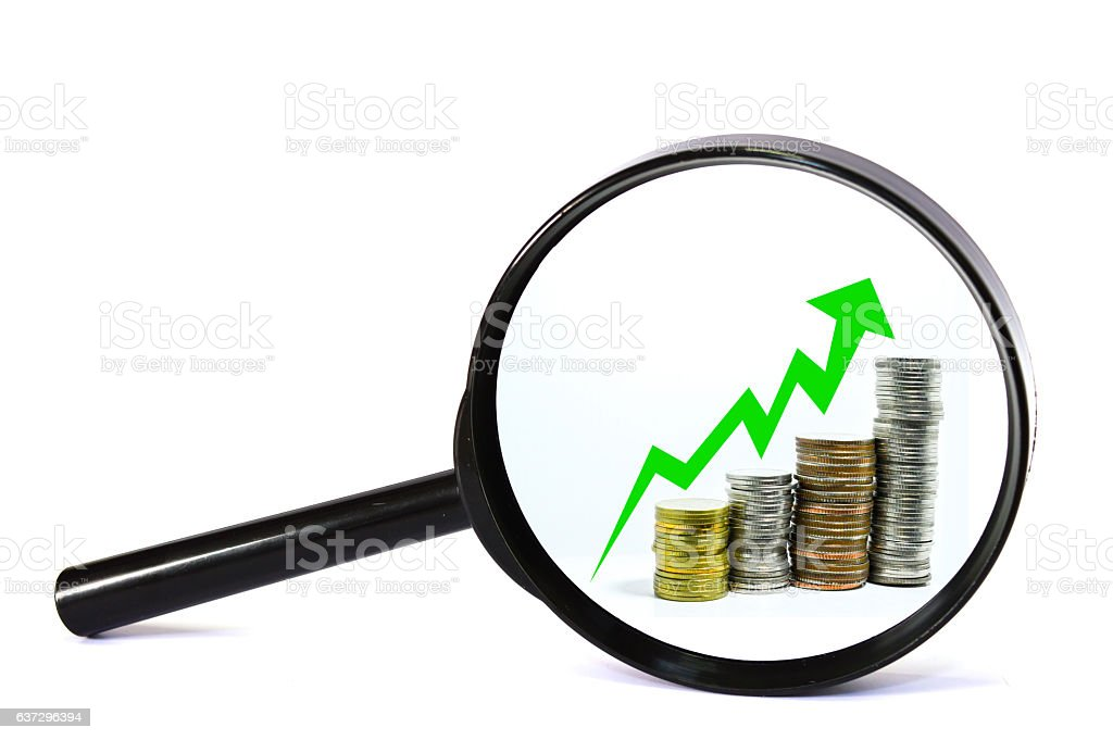 magnifying glass concept green arrow uptrend on coin stock photo