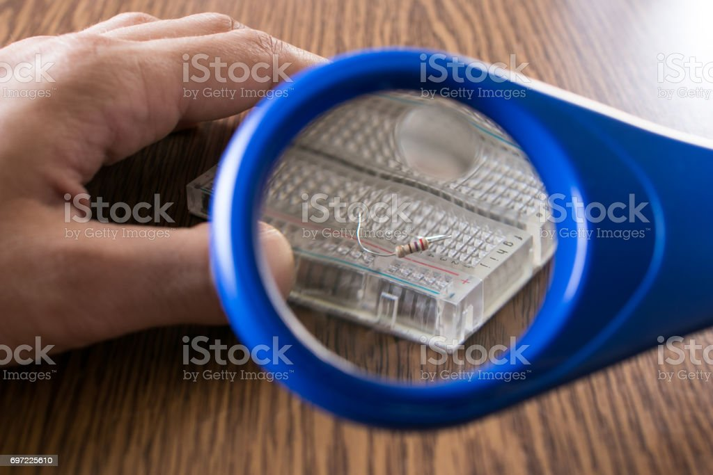 Magnifying glass enlarges a resistor stock photo
