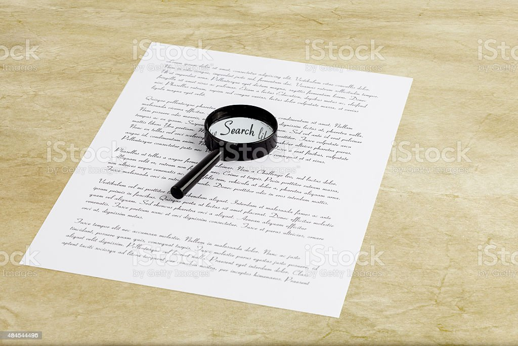 Magnifying glass enlarging the word Search on a printed text stock photo