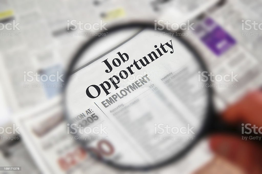 Magnifying glass focusing on classifieds section stock photo