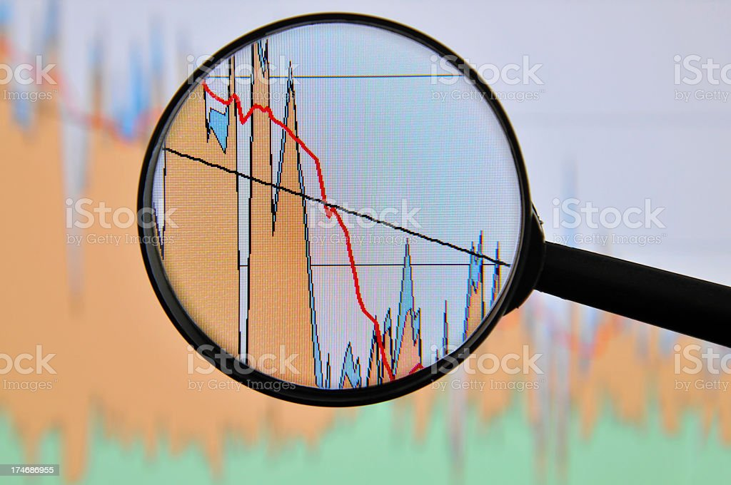 Magnifying glass, graph pictured on computer screen is going down royalty-free stock photo